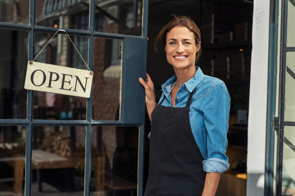 "Happy owner in front of her business with an ""Open"" sign"